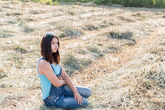 Pensive teen girl in a field with str. Aw Stock Images