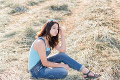 Pensive teen girl in a field with str. Aw Stock Photography