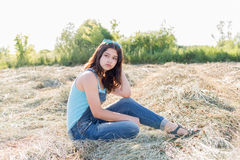 Pensive teen girl in a field with str. Aw Stock Image