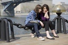 Pensive teen girls sitting at river Stock Photo