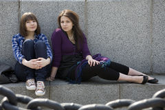 Pensive teen girls sitting at river Stock Photos