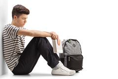 Pensive teen student leaning against a wall. Pensive teen student sitting on the floor and leaning against a wall isolated on white background Stock Image