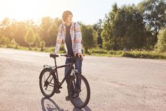 Pensive teenage boy standing on road, keeping hand on handle bar of his bike, waiting for others cyclists to have journey together. Looking aside while Stock Photos