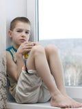 Pensive teenage drinking tea. stock photos