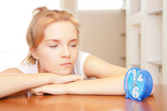 Pensive teenage girl with clock Stock Images