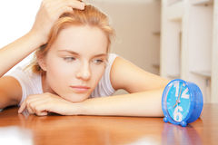 Pensive teenage girl with clock Royalty Free Stock Photos