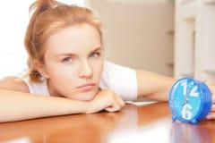 Pensive teenage girl with clock Stock Photography