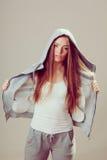 Pensive teenage girl in hooded sweatshirt. Fashion Stock Image