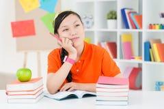 Pensive teenage girl. Image of a pensive teenage girl sitting at a table stock image