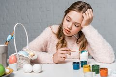 Teenage girl painting easter egg and looking at basket stock photos