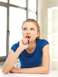 Pensive teenage girl with pen and paper stock photos