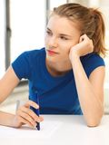 Pensive teenage girl with pen and paper royalty free stock photos