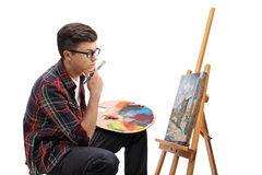 Pensive teenage painter looking at a painting. Profile shot of a pensive teenage painter looking at a painting isolated on white background Stock Image
