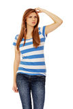 Pensive teenage woman scratching her head Royalty Free Stock Photos