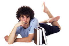 Pensive teenager with books. Pensive teenager with books lying on the floor and has downcast appearance.  on white Stock Photo