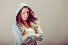 Pensive teenager girl in hood crossing arms. Stock Photography