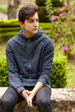 Pensive teenager guy in a park Stock Photography