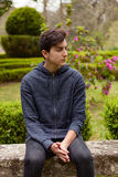 Pensive teenager guy in a park Royalty Free Stock Photography