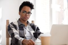 Pensive thoughtful african-american woman thinking of problem solution at work stock images