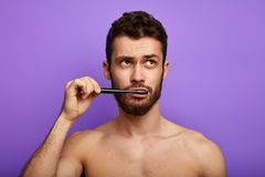 Pensive thoughtful sexy guy looking aside and brushing his teeth stock photos