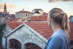 Pensive thoughtful woman tourist looking at beautiful cityscape of old Europe town with orange tile roofs  at sunset during travel. Pensive thoughtful woman Stock Photos
