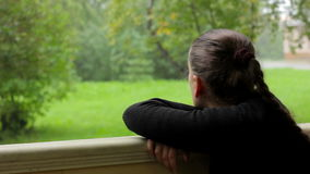 Pensive thougtful girl watching the rain on the background of greenery at park stock video footage