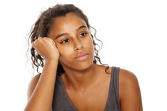 Pensive and tired. Dark skinned beautiful girl on a white background leaning on her hand Royalty Free Stock Photography