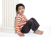 Pensive Toddler Sitting Against a Column Royalty Free Stock Photo