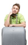 Pensive tourist leaning on travel suitcase Royalty Free Stock Images
