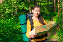 Pensive tourist with map in a forest. Pensive tourist with map in a summer forest Royalty Free Stock Photos