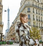 Pensive trendy fashion-monger with Christmas tree in Paris Royalty Free Stock Images