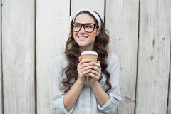 Pensive trendy woman with stylish glasses holding coffee Stock Images