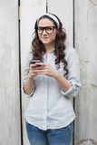 Pensive trendy woman with stylish glasses sending text message Stock Image