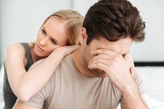 Pensive unhappy woman comfort her sad man while they sitting in bed. Carefree blonde women comfort her sad crying men while they sitting in bed at home stock photo