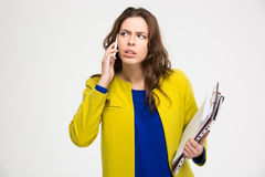 Pensive unpleased young woman with clipboad talking on mobile phone Royalty Free Stock Photography
