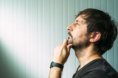 Pensive unshaven man with hand on chin making decision. Judging or evaluating something, studio profile portrait with copy space Royalty Free Stock Photos
