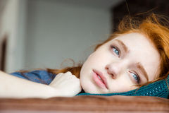 Pensive upset young woman lying on knitted pillow Royalty Free Stock Photo
