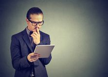 Pensive using tablet and taking decision. Formal man in glasses touching lips brainstorming an idea while surfing tablet computer and building strategy Stock Photos