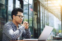 Web developer working in cafe. Pensive Vietnamese web developer looking laptop screen stock photos