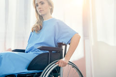 Pensive wheelchair woman in hospital chamber. Side view of pensive wheelchair woman in hospital chamber Royalty Free Stock Photography