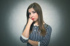 Pensive sad woman portrait. Pensive wistful woman is wondering and thinking on gray background. Disappointed girl royalty free stock image