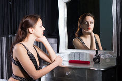 Pensive wistful young woman. Pensive glamorous wistful young woman in evening wear sitting at her dressing table reflected in the mirror with a look of longing Stock Photo