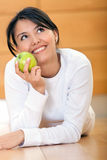 Pensive woman with an apple Stock Photography