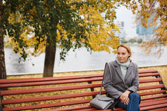Pensive woman in autumn park near river Stock Image