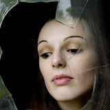 Pensive woman behind a broken window. Royalty Free Stock Photo
