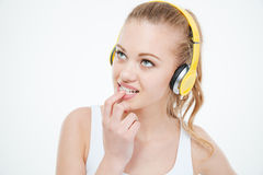 Pensive woman biting nails and listening to music in headphones Royalty Free Stock Photos