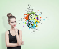 Pensive woman in a black tank top, light bulb Stock Image