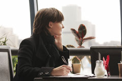 Pensive woman in black working in cafe. Young pensive woman in black working in cafe with papers Royalty Free Stock Photos