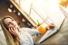 Pensive woman blogger working at a laptop and talking about something on the phone. While sitting at a table with a glass of orange juice near a large window in Royalty Free Stock Photo