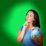 Pensive woman with a blue money-box. On a over green background royalty free stock photo